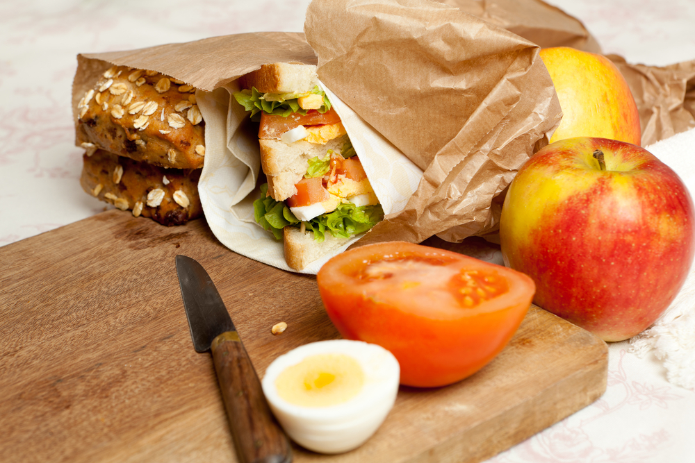 Fruit, sandwiches and buns in a brown bag