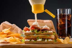 Pouring mayonnaise on sandwich with meat, cheese and vegetables